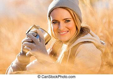mujer joven, calentamiento, con, café