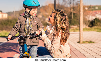 mujer joven, con el niño, encima, bicicleta, en, día soleado