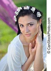 mujer joven, con, flores del resorte, en, ella, pelo