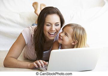 mujer joven, con, niña, usar la computadora portátil,...