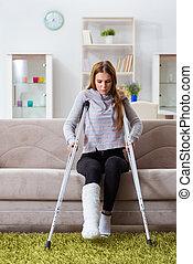 mujer joven, con, pierna rota, en casa