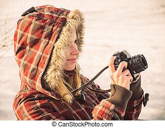 mujer joven, con, retro, cámara fotográfica de la foto, al aire libre, hipster, estilo de vida, con, naturaleza del invierno, fondo