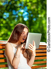 mujer joven, con, tableta de digital, en el parque