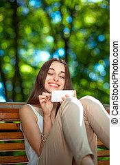 mujer joven, con, teléfono móvil, en el parque