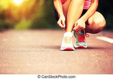 mujer joven, corredor, atar cordones