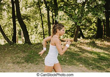 mujer joven, corriente, en el estacionamiento, en, hermoso, día de verano