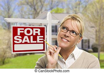 mujer joven, delante de, muestra vendida, y, casa
