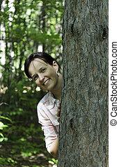 mujer joven, echar una ojeada, de atrás, un, árbol