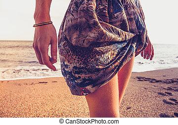 mujer joven, en, colorido, falda, ambulante, en la playa
