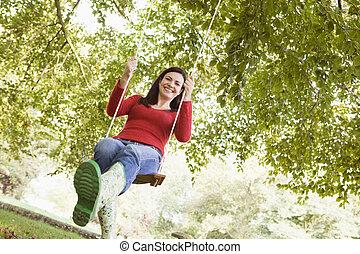 mujer joven, en, margen de crédito de árbol