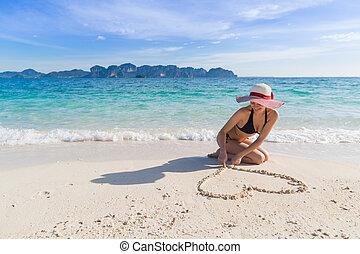mujer joven, en, playa, vacaciones del verano, niña, empate, forma corazón, acostado, arena, playa