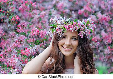 mujer joven, en, un, parque, con, un, primavera, guirnalda