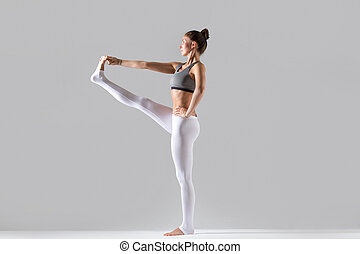 mujer joven, en, utthita, hasta, padangustasana, postura, gris, estudio, ba