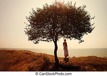 mujer joven, en, vestido del verano, posición, cerca, árbol, y, mirar, a, mar, teñido, foto