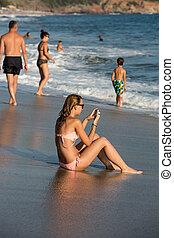 mujer joven, es, el sentarse en la playa, en, salida del sol