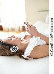 mujer joven, escuchar, música, acostado, en, un, cama