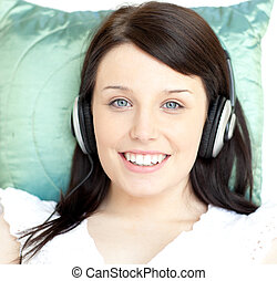 mujer joven, escuchar, música, acostado, en, un, sofá