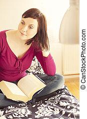 mujer joven, leer un libro, en cama