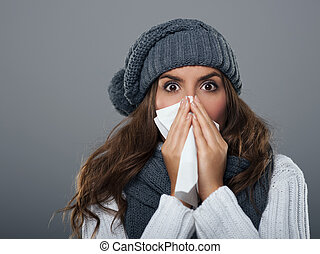 mujer joven, llevando, tibio, sombrero, estornudar