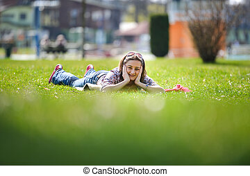 mujer joven, mentira en la hierba, en, el, summer., relajante, aire libre, mirar, feliz, y, sonreír., natural, felicidad, diversión, y, armonía