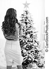 mujer joven, posición, delante de, árbol de navidad, ., vista trasera