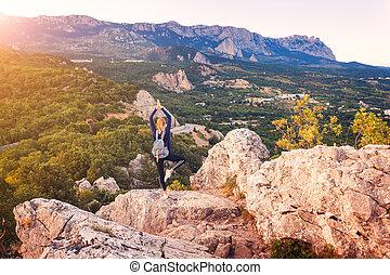 mujer joven, posición, en, el, pico de la montaña, en, ocaso