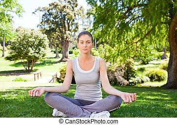 mujer joven, practicar, yoga, en el parque