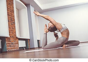 mujer joven, practicar, yoga, en, estudio