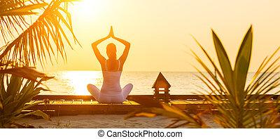 mujer joven, practicar, yoga, en la playa, en, ocaso