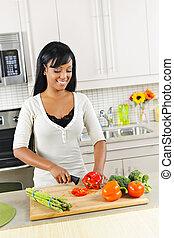 mujer joven, se cortar verduras, en, cocina