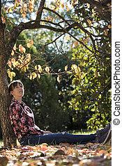 mujer joven, sentado, debajo, otoño, árbol, reclinado, su, tronco