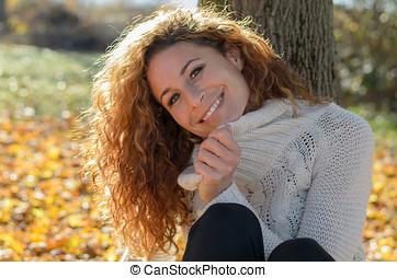 mujer joven, sentado, delante de, un, árbol