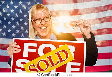 mujer joven, tenencia, teclas de casa, y, muestra vendida, delante de, bandera estadounidense