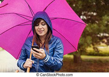 mujer joven, texting, en, teléfono móvil, en la lluvia