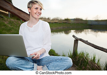 mujer joven, usar la computadora portátil, aire libre