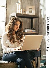 mujer joven, usar la computadora portátil, mientras, sentado, en, apartamento pajar