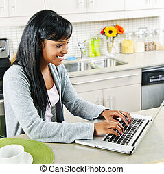 mujer joven, usar ordenador, en, cocina