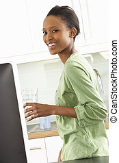 mujer joven, usar ordenador, en, moderno, cocina