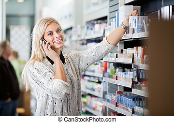 mujer joven, utilizar, teléfono móvil, en, farmacia
