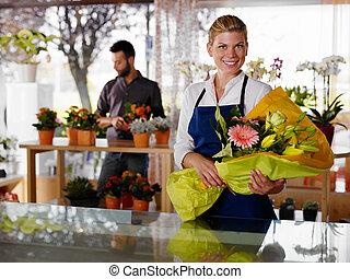 mujer joven, y, cliente, en, flores, tienda