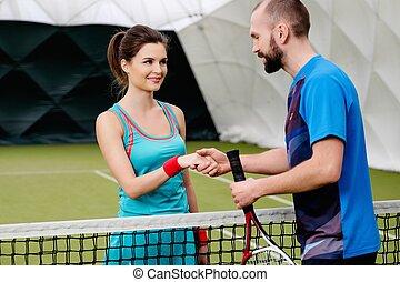 mujer, jugador del tenis, sacudarir la mano, con, ella, entrenador