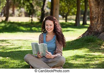mujer leer un libro, en el jardín