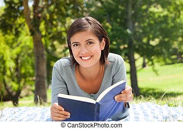 mujer leer un libro, en el parque