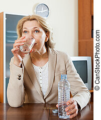 mujer madura, agua potable