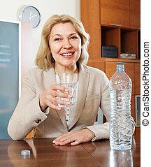 mujer madura, agua potable, de, vidrio