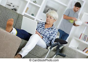 mujer madura, con, herido, pierna, relajante, sofá