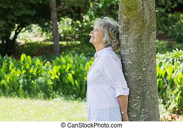 mujer madura, inclinar, tronco de árbol, en el estacionamiento