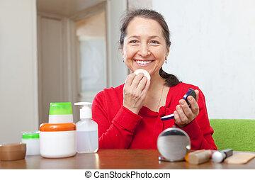 mujer madura, poniendo, facepowder, en, cara