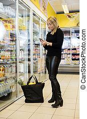 mujer madura, utilizar, teléfono móvil, en, tiendade comestibles