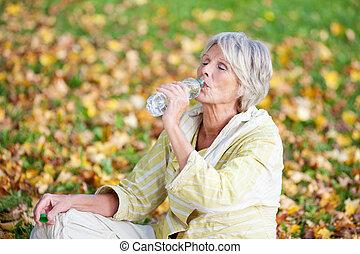 mujer mayor, agua potable, en el estacionamiento